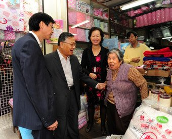 Executive Director (Operations & Project Control) of the URA, Calvin Lam (first left) and Director (Acquisition & Clearance) of the URA, Joseph Lee (second left) talking to one of the shop operators.
