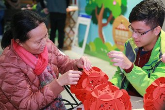 Participating student volunteer and beneficiary of CSPS make Lunar New Year decorations at one of the Chinese handcraft workshops to embrace the approach of the Year of the Dog.